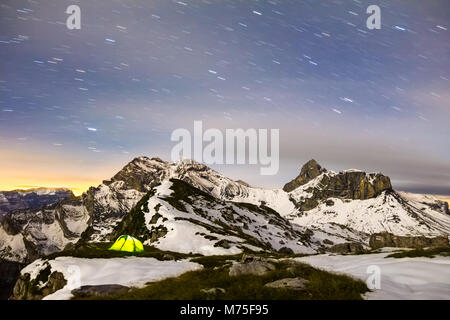 Tent glows under a starry night sky in snowy alpine mountains. Alps, Switzerland. - Stock Photo
