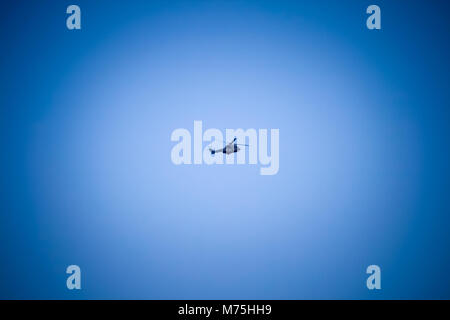Military Helicopter flying in a deep blue sky with vignette - Stock Photo