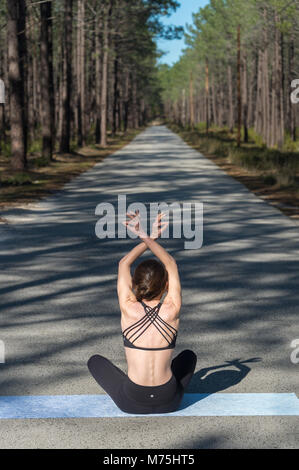 woman sitting on a yoga mat meditating in the middle of a road in a forest - Stock Photo