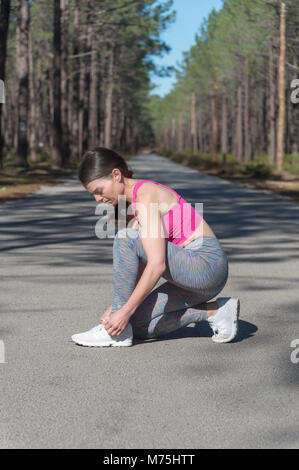 woman jogger tying up her laces on trainers - Stock Photo