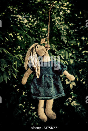 toy rabbit hanging  from a rope noose in a wood - Stock Photo