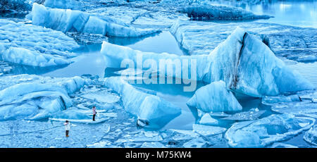 Jokulsarlon glacier lagoon panorama at dawn, in Iceland. Unidentifiable tourists walk on thin ice to photograph - Stock Photo