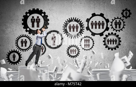Businessman playing fife while standing on pile of documents among flying papers with social gear structure on background. - Stock Photo