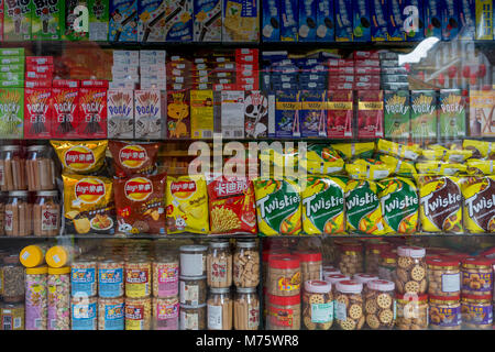 A detail of assorted snacks including biscuits, crisps and other merchandise on shelves in a corner shop (convenience - Stock Photo