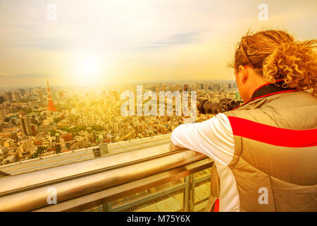 Traveler photographer takes a picture of Tokyo Skyline and Tokyo Tower, Minato District, Tokyo, Japan. Japan travel - Stock Photo