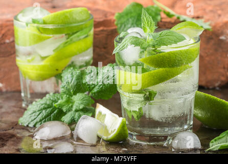 Mojito cocktail or lemonade with lime, mint and ice cubes. Traditional summer refreshing drink. Selective focus - Stock Photo