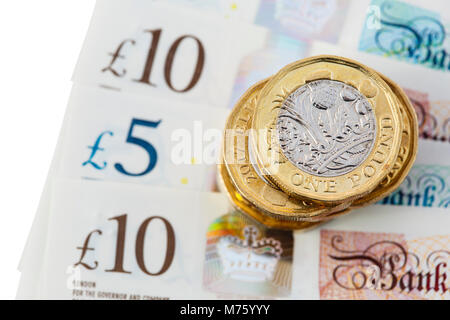 Pile of British 12 sided one pound coins money sterling pounds on new polymer £10 and £5 notes GBP close-up on a - Stock Photo