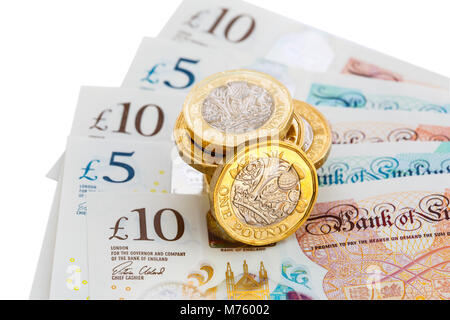 Pile of British 12 sided £ one pound coins money sterling pounds cash on new polymer plastic £10 and £5 notes GBP - Stock Photo