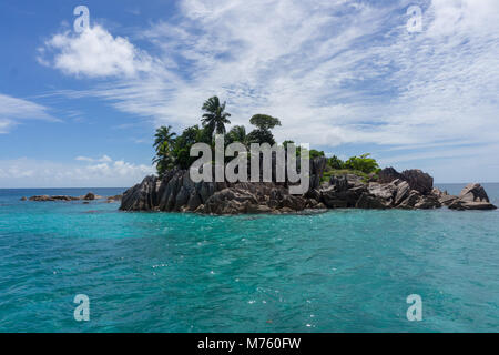 St Pierre granitic island in the Seychelles on a sunny day, surrounded by turquoise water, coral and tropical fish. - Stock Photo