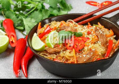 Spicy starch (rice, potatoes) noodles with beef and vegetables - bell peppers, carrots, zucchini, sesame, lime, - Stock Photo