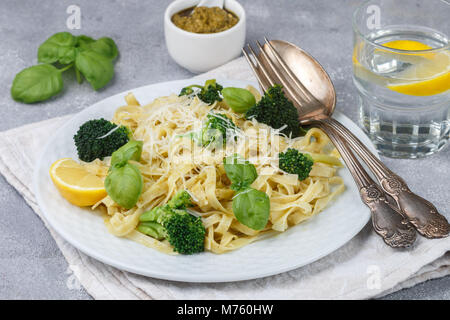 Homemade fresh pasta with pesto and broccoli with cheese and Basil. Tagliatelle. A delicious gourmet dinner. Selective - Stock Photo