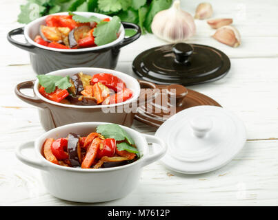 Baked vegetables in portion pots. Eggplant, bell pepper, carrot, onion, garlic, cilantro. Vegetarian dish. Selective - Stock Photo