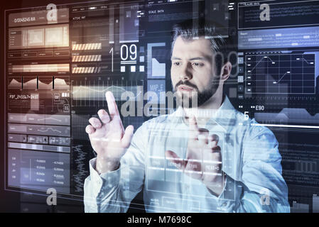Careful specialist working alone in his office and looking concentrated - Stock Photo