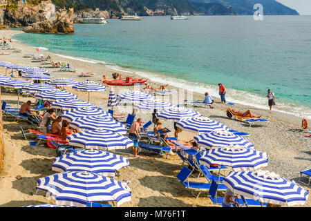 The sandy beach at Monterosso Al Mare, Cinque Terre Italy, with umbrellas, sunbathers, the Ligurian sea and boats - Stock Photo