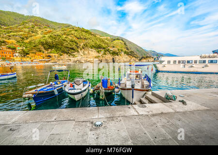 Boats line up at the pier in the seaside village of Monterosso al Mare, Cinque Terre Italy with the hills, town - Stock Photo