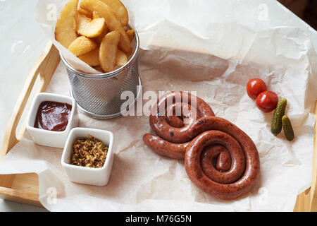 Grilled sausages with potatoes in rustic style with two kinds of sauces.On parchment paper - Stock Photo