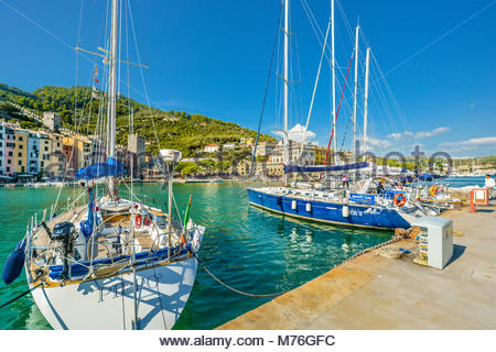 Sailboats line up in the harbour and marina of Portovenere Italy with the town and coast behind on a sunny day in - Stock Photo