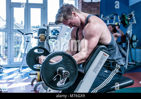 Muscular man working out with weights in the gym - Stock Photo