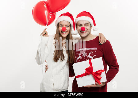 Christmas Concept - Young caucasian couple holding gifts,champnage and balloon making funny face on Christmas. - Stock Photo