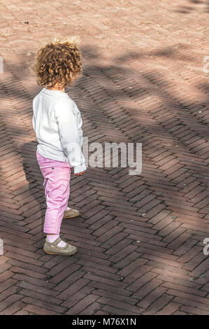 little girl with brown curly hair standing on the street - Stock Photo