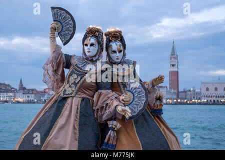 Women in traditional costumes and masks, with decorated fans, at San Giorgio, with St Marks and bell tower in the - Stock Photo