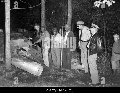 Law enforcement officials investigate the scene of an illegal backwoods moonshine still in rural Georgia, ca. 1955. - Stock Photo
