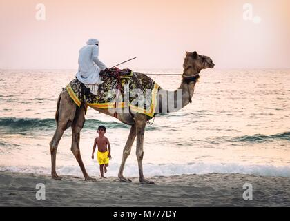 Boy stares in amazement at Arabic man wearing a thawb riding a camel on a beach, Dubai, United Arab Emirates, Middle - Stock Photo