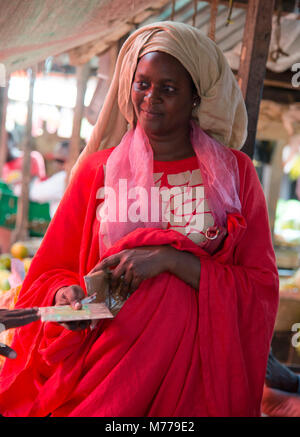 A colourfully dressed woman in the market in Stone Town, Zanzibar, Tanzania, East Africa, Africa - Stock Photo