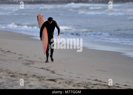 Surfer leaving the beach - Stock Photo