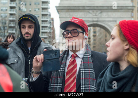 - New York, NY, USA. 8March 2018 Man in a red Make America Great Again hat (MAGA) records activists durig a rally - Stock Photo