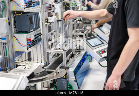 08 March 2018, Germany, Esslingen: Apprentices work on a small-scale model of a modern car assembly and production - Stock Photo