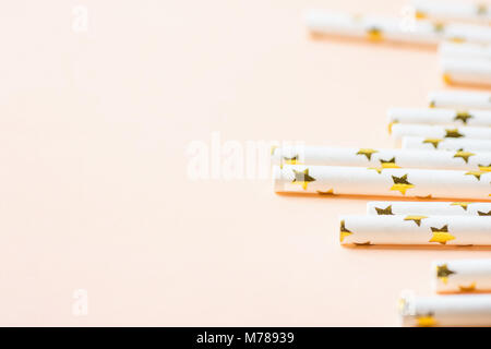 Elegant White Paper Drinking Straws with Golden Stars Pattern Scattered on Peachy Pink Background. Low Angle. Birthday - Stock Photo