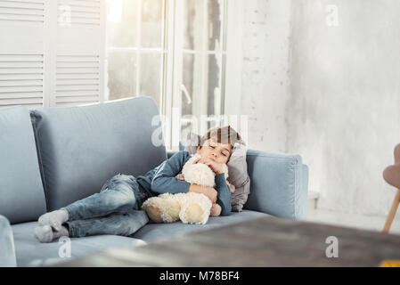Adorable little boy sleeping with his toy Stock Photo