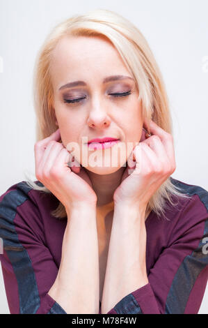 Relaxation and meditation techniques. Young blonde closed eyes woman holding earlobes with fingers. - Stock Photo