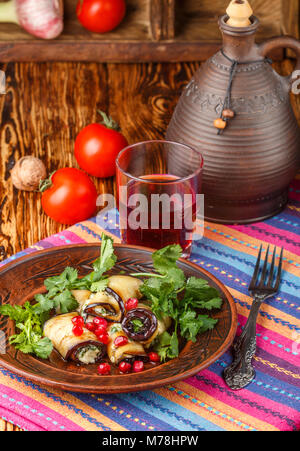 Rolls of fried eggplant with cheese, garlic, cilantro and pomegranate seeds. Gourmet appetizer. Selective focus - Stock Photo