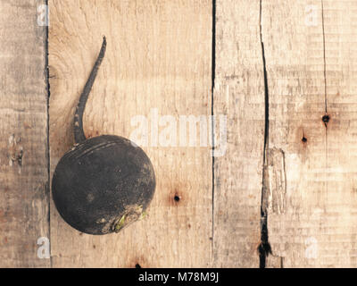 Black winter radish on a rustic wooden table, view from above with space for text or image - Stock Photo