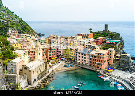 The small fishermen village of Vernazza, with its colorful houses and its church around its little port, is one - Stock Photo