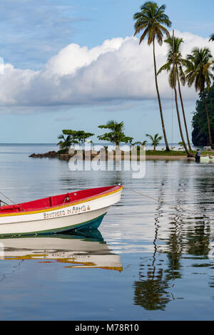 Traditional fishing boat moored at Marigot Bay with tall palms on the small beach in the distance, St. Lucia, Windward - Stock Photo
