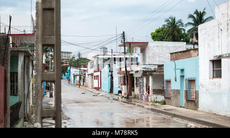 Holguin, Cuba - August 31, 2017: A man cleans the sidewalk in front of a home after a rainstorm. - Stock Photo