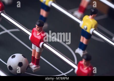 horizontal closeup with selective focus of red shirt player figurine with ball at his feet on foosball table soccer - Stock Photo