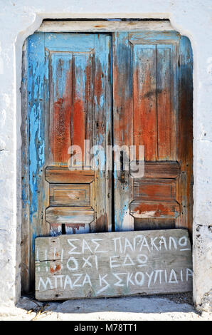 Santorini / Greece - March 7, 2011: An old damaged blue door on the island of Santorini, Greece - Stock Photo