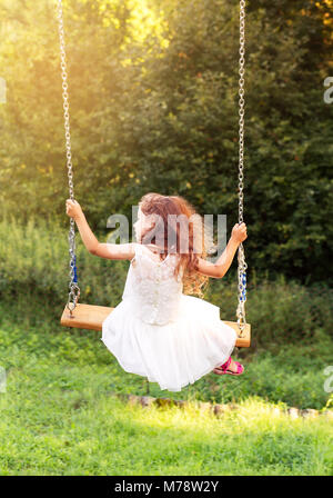 Happy beautiful little girl sitting on seesaw at summer day, back view - Stock Photo