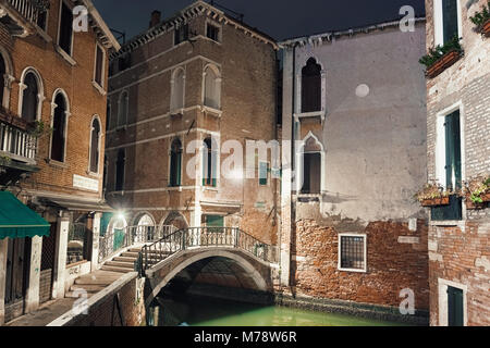 VENICE, ITALY - DECEMBER 23, 2017: Empty street with a bridge over a water channel in Venice in the night - Stock Photo