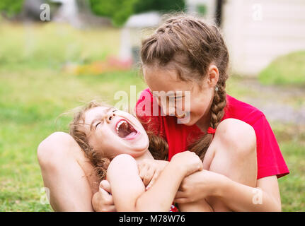 Two Happy little girls embracing and laughing at the park - Stock Photo