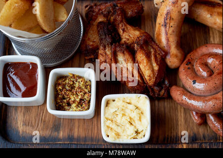 German hearty lunch in the pub.Grilled sausages, stewed cabbage, croutons, sauce. Beer snack - Stock Photo