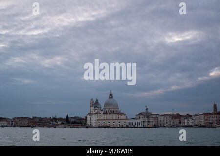 View of Basilica di Santa Maria della Salute and Grand Canal. Photo taken on a cloudy day with sun trying to break - Stock Photo