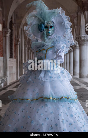 Masked woman in highly ornate white and aqua coloured costume and hat, standing under the arches at the Doges Palace - Stock Photo
