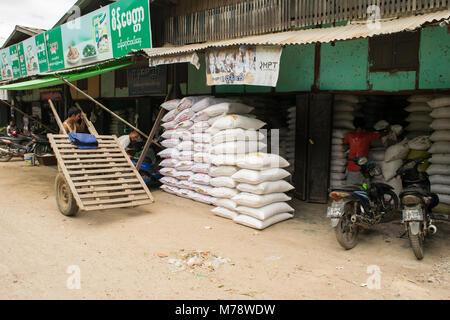A vendor at Nyaung U market selling sacks of rice or flour. Burmese man with makeshift wooden cart with car tires - Stock Photo