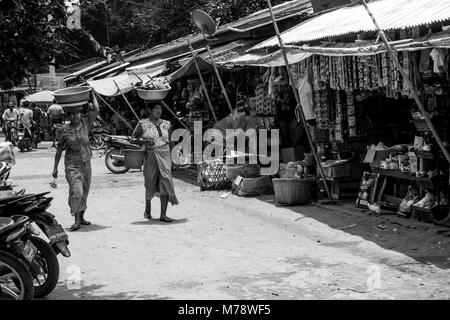 Two Burmese women, shopping in Nyaung U local market, head-carrying balancing a basin with groceries on their head - Stock Photo