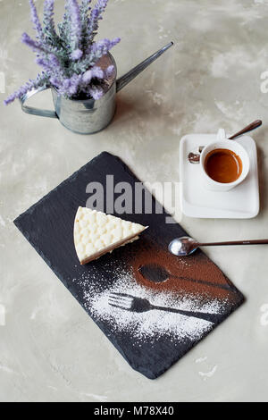 The outline of the fork and spoon , sprinkled with cocoa powder. Three chocolate cake on a stone stand and coffe - Stock Photo